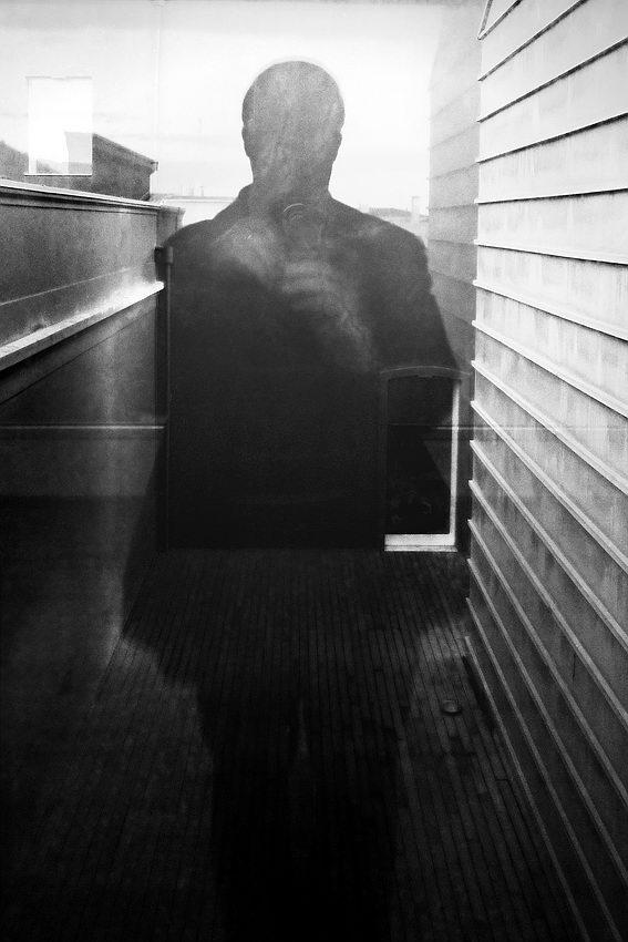 Reflexo do fotografo num vidro e fusão da sombra com o ambiente