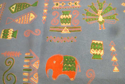 Tablecloth detail with red elephant and green peacock