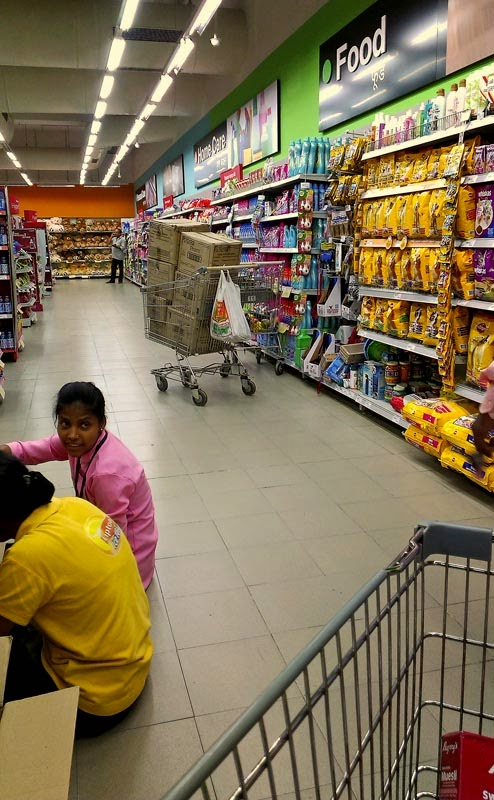 Supermarket employees arranging goods