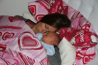 Baby schläft mit Mama im Bett