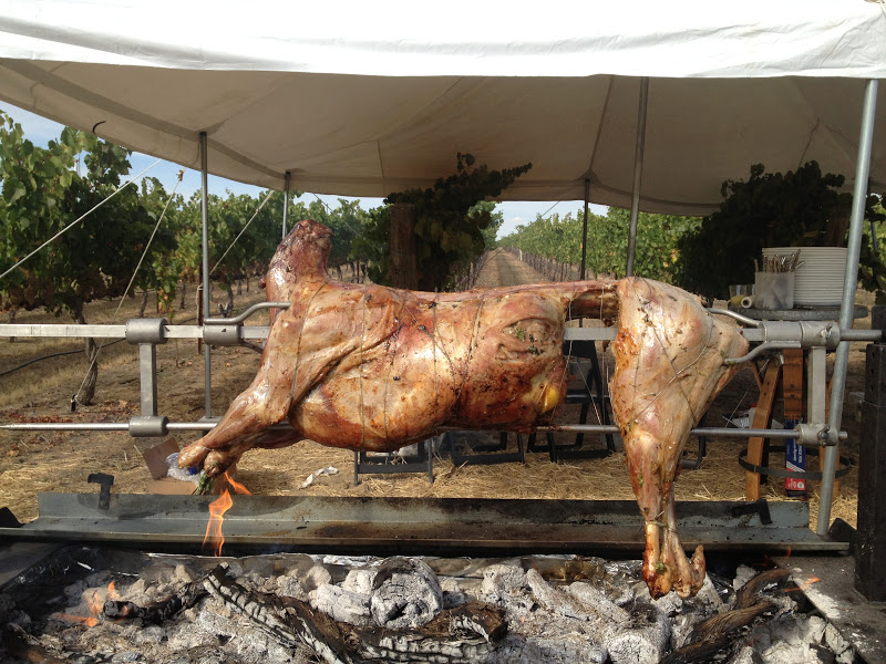 The goat was done first and taken to rest on a wood slab table.