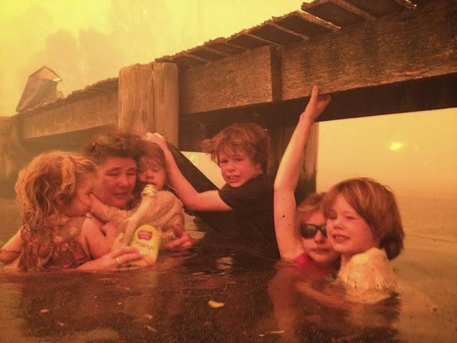 Тэмми Холмс и ее внуки укрываются под причалом во время лесного пожара в Австралии.