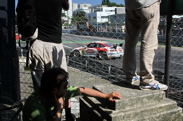 Carro numa curva, visto por entre as pernas dos espectadores