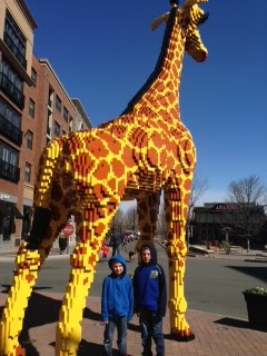 My two boys standing under the giant Lego giraffe