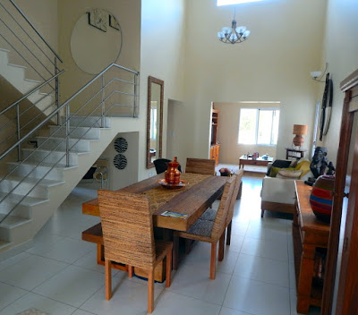 A mesma sala de jantar, vista no entanto a partir da cozinha, com a sala de TV em último plano. A iluminação e a ventilação natural dos ambientes gera economia no consumo de energia.