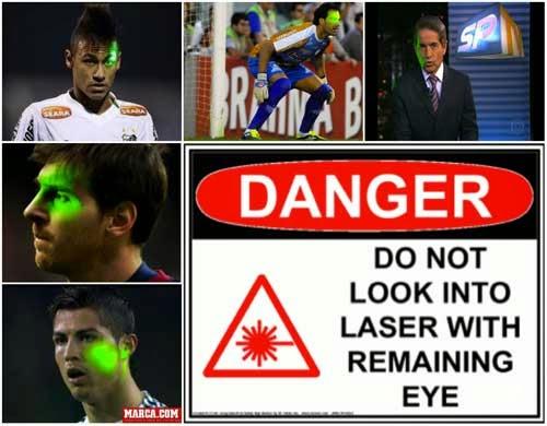 Montagem de fotos com os jogadores Neymar, Messi e Cristiano Ronaldo. Todos eles estão sendo iluminados com um laser verde. Algum torcedor faz isso para atrapalhar a visão deles. Ainda há um goleiro  preparado para defender um penalti que também está com um laser nos olhos, assim como um jornalista da Rede Globo, que está apresentando o jornal dentro do estúdio, com uma janela voltada para a rua do lado dele. Ao centro, uma mensagem de alerta para não  olhar diretamente para o laser, aviso que está colado em qualquer emissor de laser.