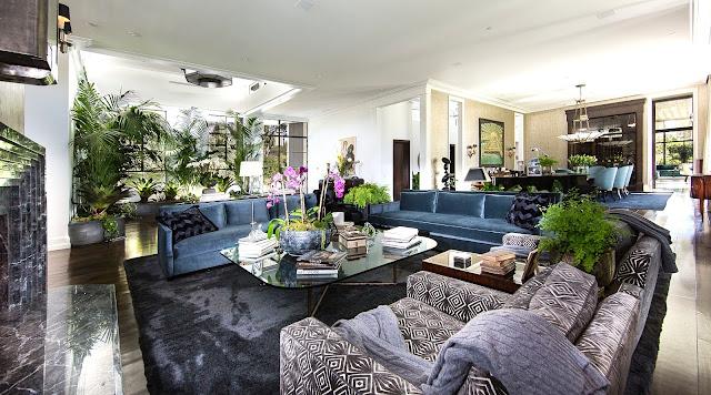 Living room blue velvet sofas dark wood floor velvet rug graphic print armchair marble fireplace