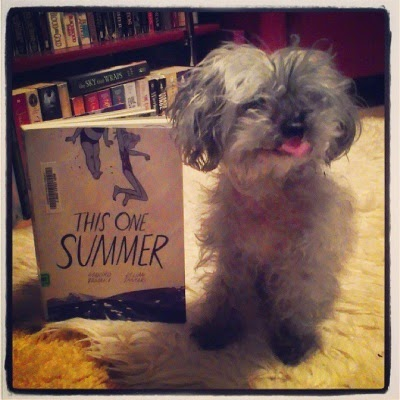 Murchie sits on a sheepskin rug. Beside him, propped upright, is a trade paperback copy of This One Summer. Its cover depicts two young girls leaping into a lake.