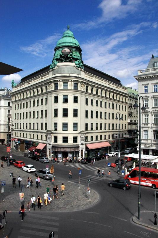 Vista de cima, do patamar do Museu Albertina, sobre a praça. Em primeiro plano os peões e os automóveis e como fundo os edifícios grandiosos