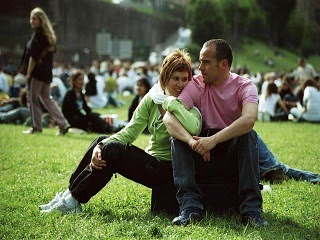 A wife holding her husband while they are in the park.