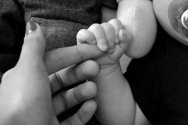 Baby hält Mamas Finger