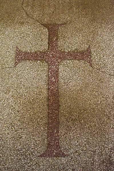 Mosaic of a red cross on a church floor with cracks