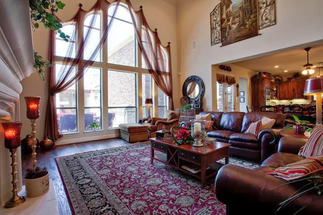 great view of the living room area with chocolate furnishings and huge windows and accent thin curtains