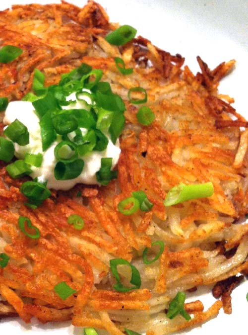 A simple, yet tasty way to eat your crispy breakfast hash browns is with a dollop of sour cream and scallions.