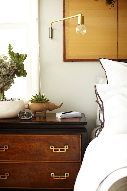 Bedroom after makeover white bedding with brown trim brass and gold accessories wood nightstand succulents