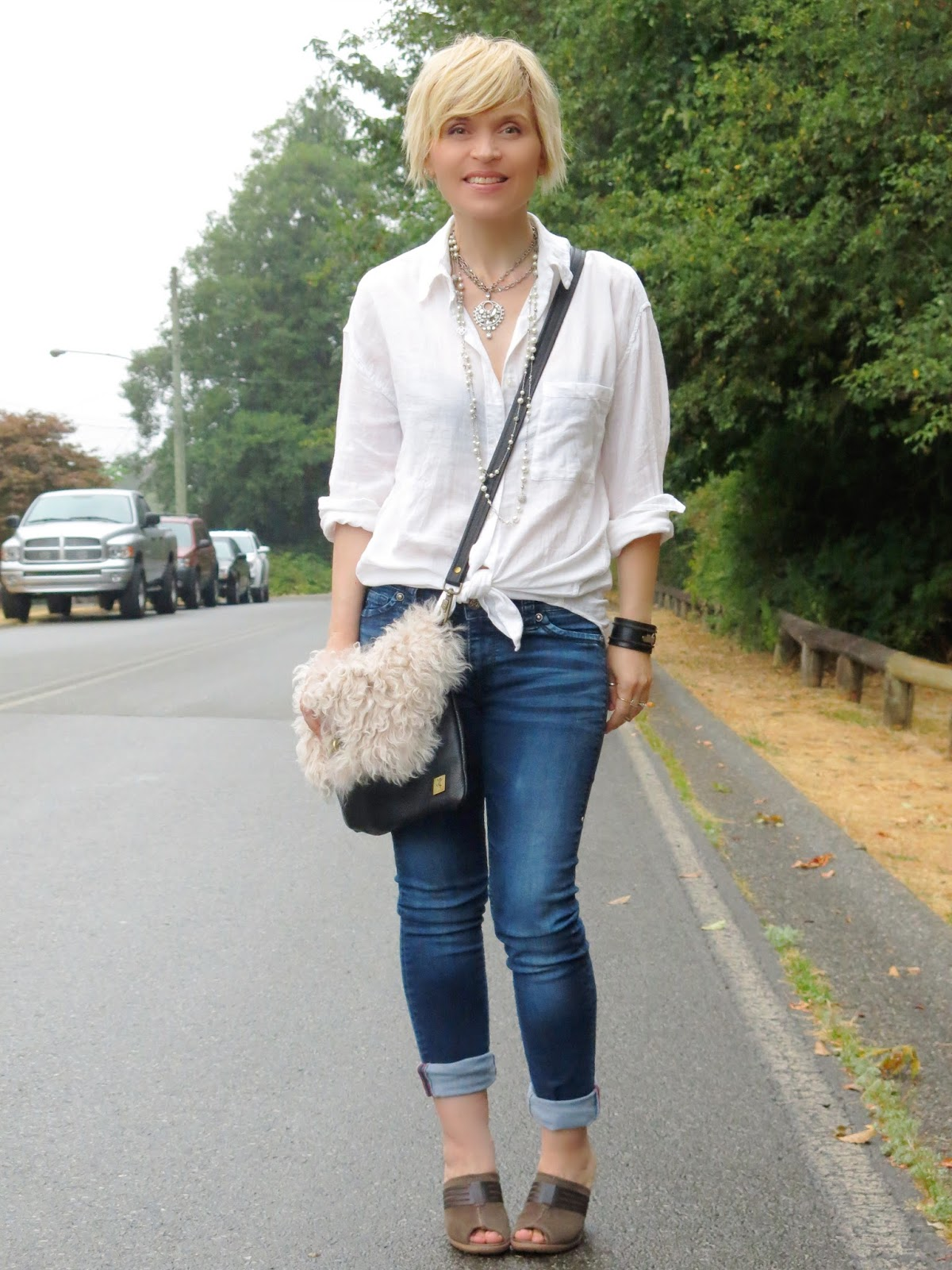 styling a white shirt with blue denim skinnies, open-toe mules, and a furry bag!