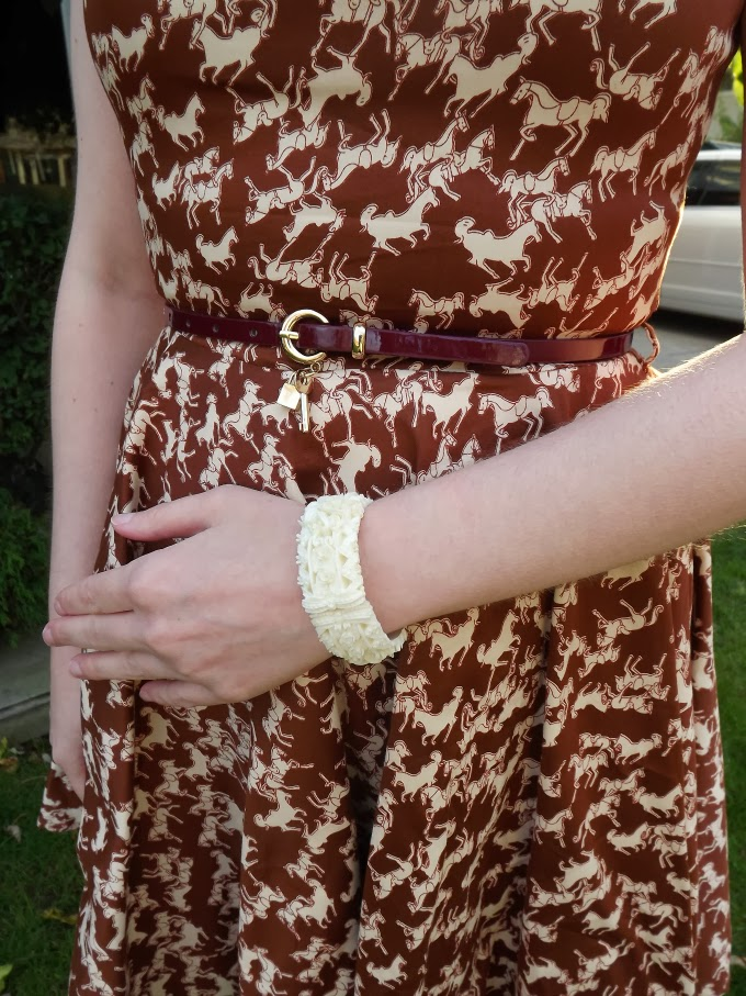 Modcloth dress, modcloth.com, Luck Be a Lady in Equine Dress, horse print, horsey print, brown dress, vintage style, close up, brown belt, lock charm, celluloid hinged banged, vintage carved cuff, ivory bangle