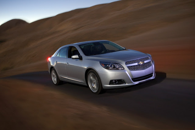 Front 3/4 view of Silver 2013 Chevrolet Malibu Turbo driving on rural road at dusk