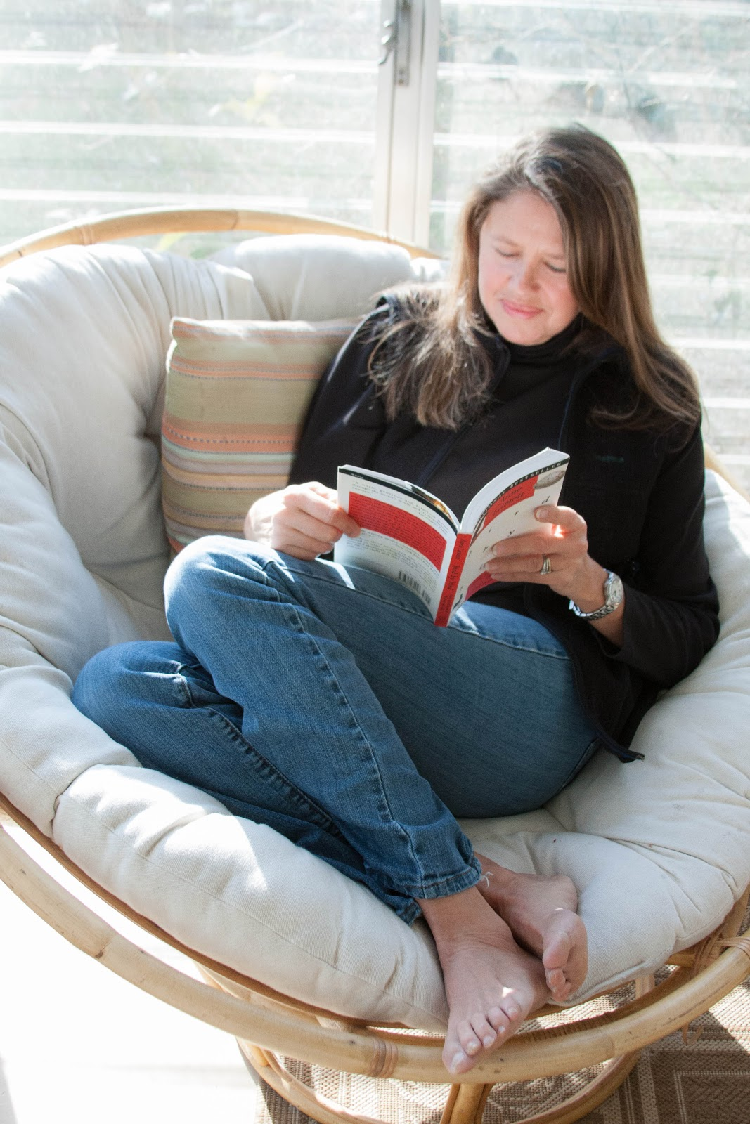 Barefoot Woman Reading In A Papasan Chair