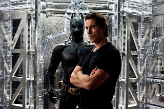 Christian Bale as Bruce Wayne in The Dark Knight Rises, standing near his new bat suit, Directed by Christopher Nolan