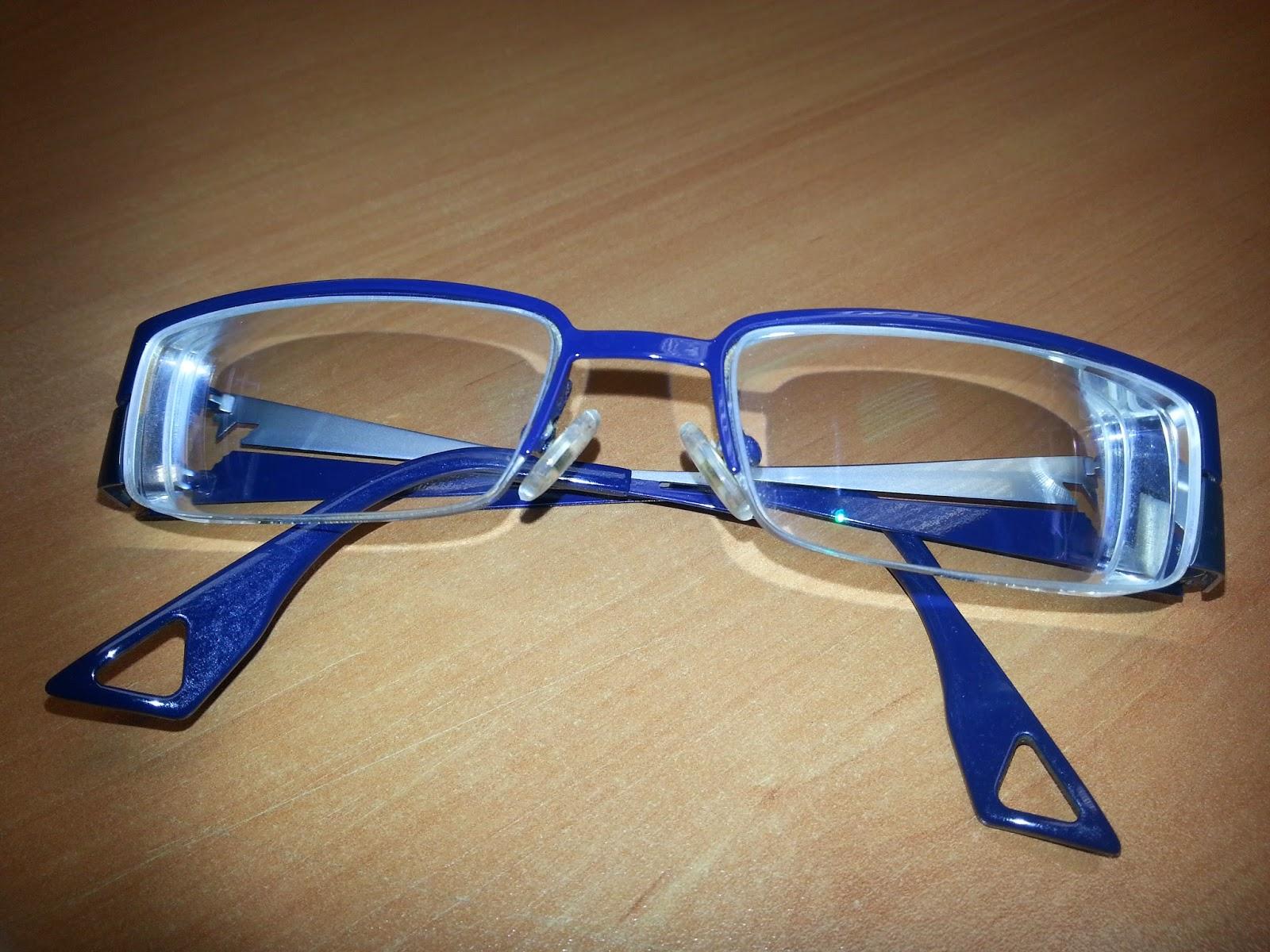 Imagen de unas gafas de montura azul encima de una mesa de madera