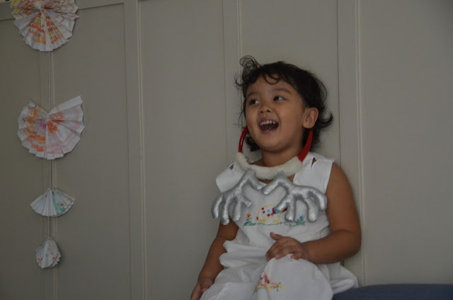 Kecil laughing from the sofa backrest