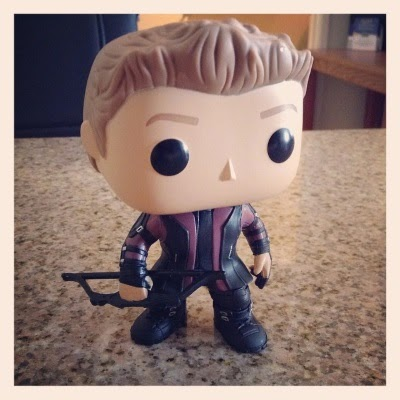 A picture of Tiny Hawkguy, a bobbleheaded white guy with pale brown hair that sticks straight up in front. He wears a purple and black leather outfit consisting of a longer jacket, pants, and boots with straps. He brandishes a tiny black bow in his right hand.