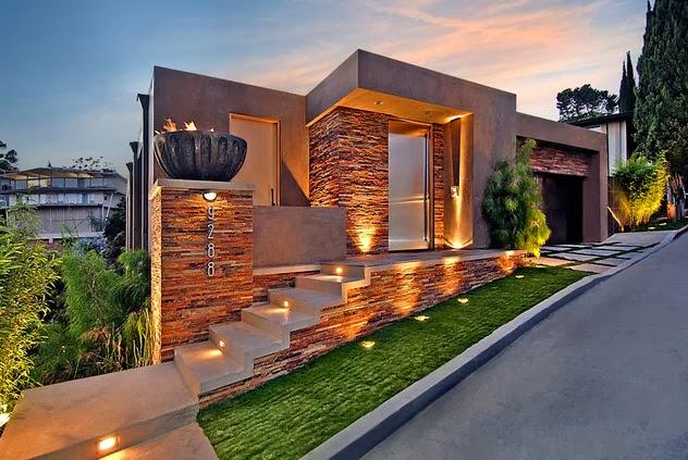 Fachada de la casa en piedra con iluminaciu00f3n prendida al anochecer ...