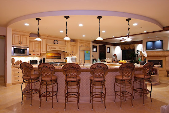 Elegant Kitchen Island With Antique Bar Stools and Chandeliers