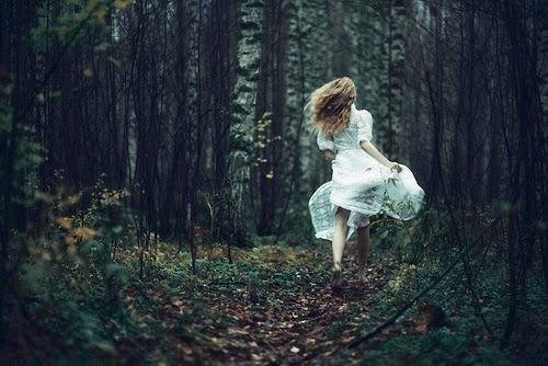 chica de blanco corriendo por un bosque