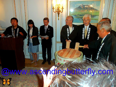 Far Left at the Podium: Mr. Kosuke Kuji, Senior Managing Director Nanbu-Bijin Co.,Ltd at drum Center: Ambassador Sumio Kusaka, Consul General of Japan in New York getting ready to break the ceremonial drum at the Ninohe City Reception