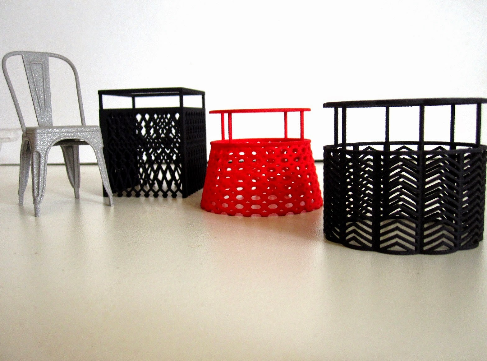 Modern dolls' house miniature 3D-printed cafe chair next to three 3D-printed tealight candle shades.