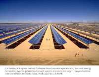 Photo of several rows of solar trough collectors in the desert