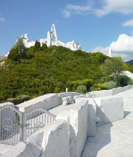 "Bright blue sky, lush greenery and brilliant white marble of ""The Heights of Eternal Hope for the Future"" hill at Kosanji Temple"