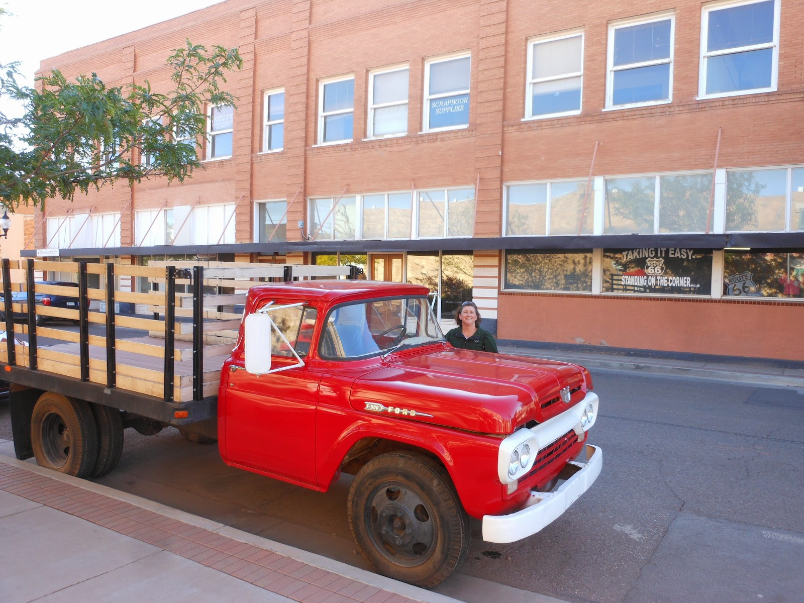 An actual red ford truck was parked on the corner funny from winslow