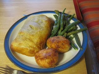 Dinner plate with individual beef wellington, green beans, and roast potatoes