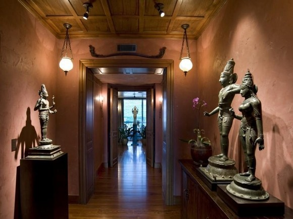 Photo of hallway with dark pink colored walls and Thai sculptures
