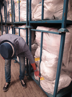 A man checking the label on a large bag of clothing on a pallet rack.
