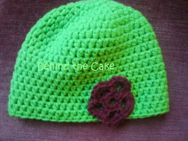 Häkelmütze aus grüner Wolle mit Häkelblume