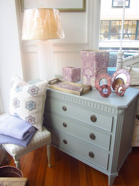 pale blue dresser with purple picture frame, serving tray and assorted boxes