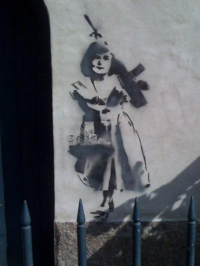 Stencil graffiti, bevæbnet pige bag jerngitter