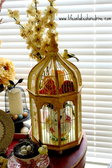 spring decor with bird cage, butterfly tea pitcher, roses, wire cloche, eggs