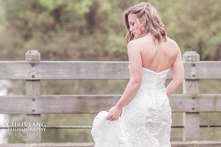 Beautiful bride in her wedding dress over looking lake at River Landing in Wallace NC.  Rustic wedding ideas