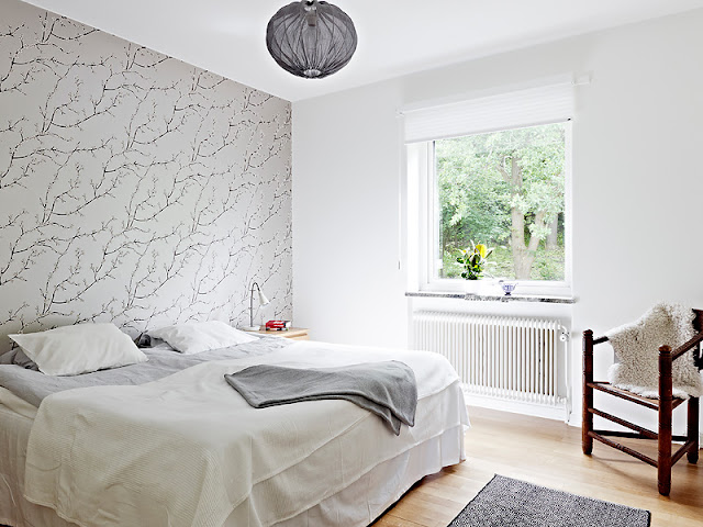 modern bedroom with one wall covered in gray wallpaper with branches on it, light wood floor, an antique chair and a window overlooking a yard
