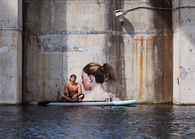 "Sean Yoro, also known as street artist Hula, is creating beautiful portraits of nude women.  He can be found floating around on a Stand Up Paddleboard (SUP) and painting away on the ""fringes"" of NYC.  Since he is testing the boundaries of legal/illegal artwork, Yoro has not disclosed the exact locations of his work.  Tides are changing though:  ""I'm getting a lot of legal walls around the world now, where I'm either permitted or commissioned to paint,"" Yoro said. ""So my plan is to just travel around the world and keep jamming on this project. This is the tip of the iceberg.""  His work is captivating and very realistic.  It's also quite an amazing feat for a person to stay balanced and focused enough to pull off this kind of work and stay dry.  You can find the original story here.  For a look at Sean Yoro, AKA Hula's work, click here."