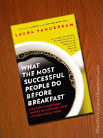 illustration of book What the Most Successful People Do Before Breakfast: And Two Other Short Guides to Achieving More at Work and at Home by author Laura Vanderkam over a wooden surface