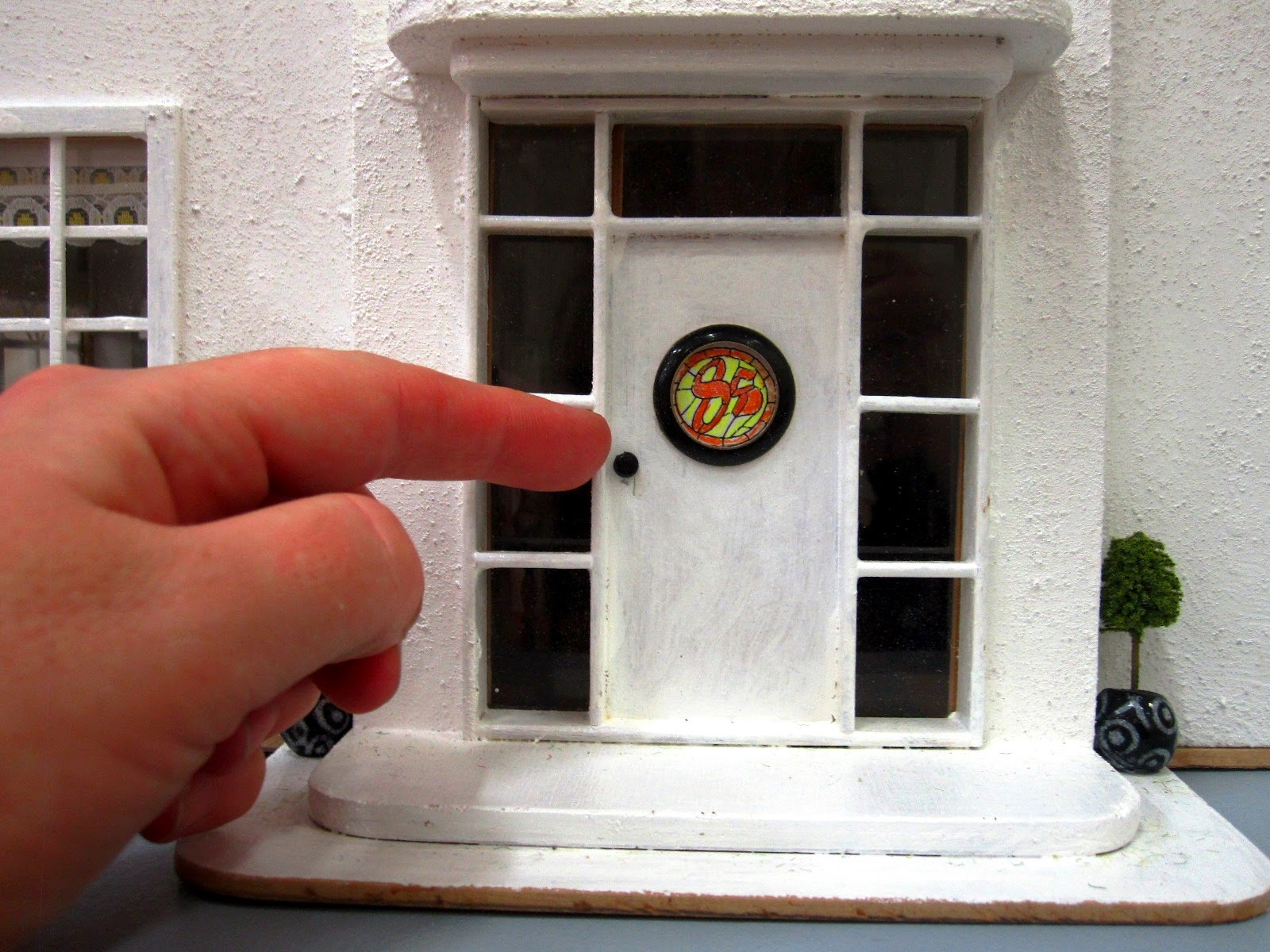 Close-up view of the front door or an Art Deco moderne-style dolls house by Anne Reid, with hand to show the scale of the house (1/24th)