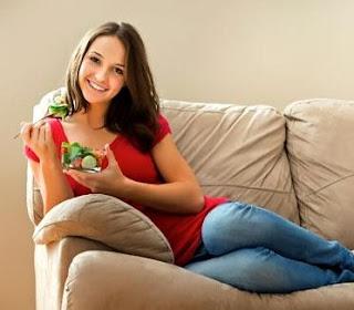 11 غذاءاً سحرياً لمحاربة النسيان - امرأة تأكل طعام وتجلس على اريكة