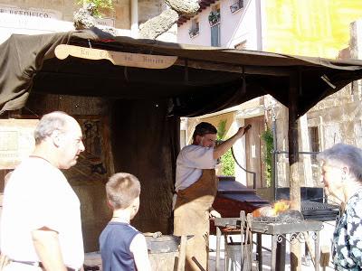 Varios viandantes contemplan los trabajos del herrero, que ha instalado su taller en un mercado medieval.