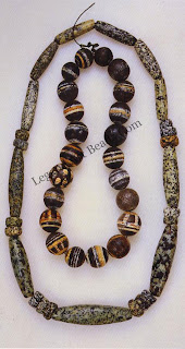 The neck-lace of elongated granite beads was made by the Dogon of Mali. Beads of hard stone have not been worked extensively in Africa, except in a few regions such as Mali and Nigeria. The round pottery beads are a contemporary creation of the Baoule people of the Ivory Coast.